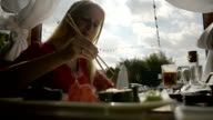 Girl eating Sushi with Chopsticks dipping in soy Sauce in a Restaurant video