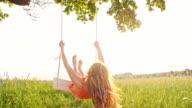 SLO MO Girl enjoys swinging on a tree swing video