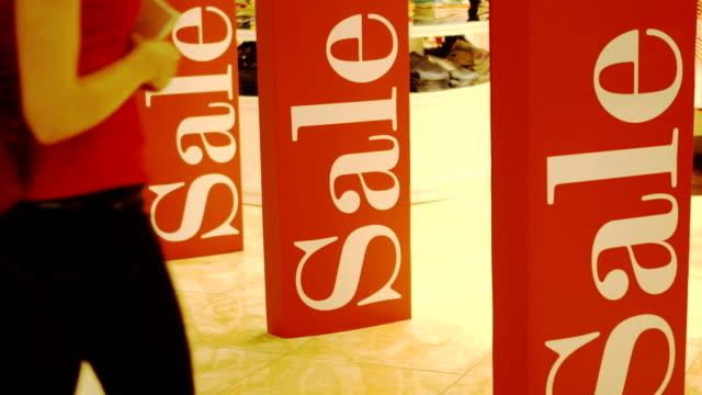 Girl entering shop. Three sales signs on shop entrance magnetic gates. Promotion. Consumerism concept video