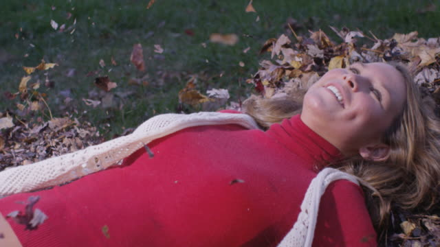 Girl falling into the autumn leaves video