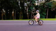 Girl five years in a helmet riding a bike. In the well-kept park on a background of trees video