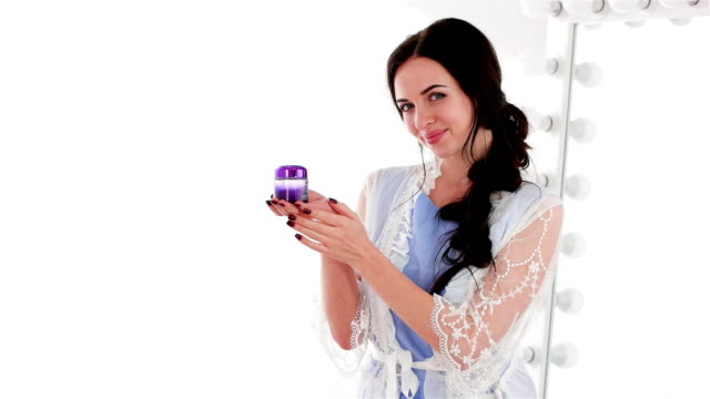girl flawless skin demonstrating violet jar of daily cream, charming lady in white negligee, natural products for healthy-looking skin video