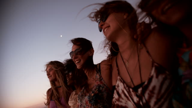 Girl friends hugging and watching the ocean after sunset video