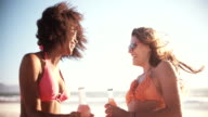 Girl friends in bikinis talking on a beach with alcopops video