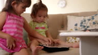 Girl Gently Shows Baby Sister Tablet Computer video