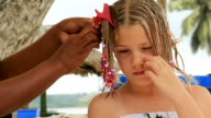 Girl gets her hair braided on tropical island vacation video