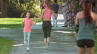 SLO MO Girl giving her mother a high five as they pass each other while running in the park video