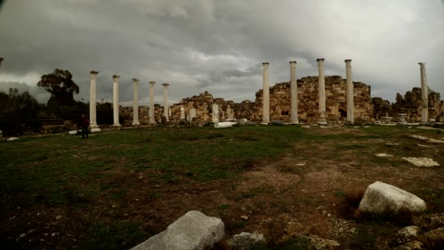 Girl goes through central square Roman Agora Cloudy day antique town Salamis Famagusta video