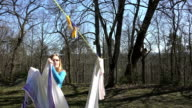 Girl hang laundry on clothesline string on forest background. video