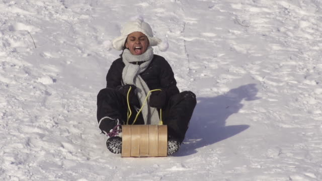 Girl has fun tobagganing on a winter day video