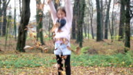 Girl having fun throwing leaves and jumping in the park video