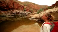 Girl hiking in the outback reads map for directions video