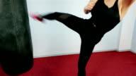 girl hits foot punching bag, dangerous woman in the gym, Beautiful Kickboxing women training in fitness studio, Beautiful brunette training video