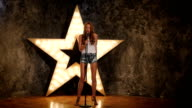 girl holding a mike and singing. shining star in the background, slow motion video