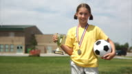 Girl holding soccer ball and trophy video