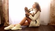 Girl hugs bengal cat on the floor. video