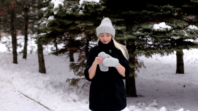 Girl in a black fur coat puts on knitted mittens. video