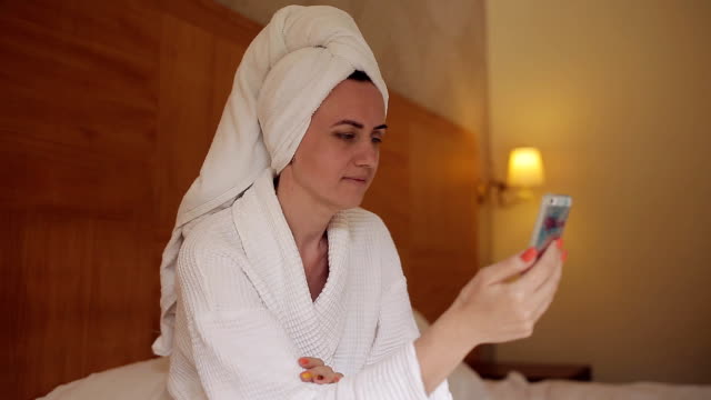 A girl in a hotel in a bathrobe sits on the bed and communicates with friends using a mobile phone video