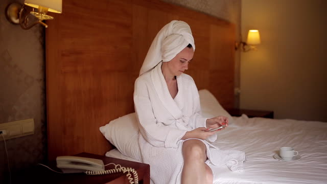 A girl in a hotel in a bathrobe sits on the bed and uses a mobile phone video