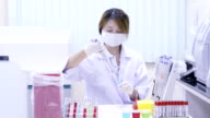 Girl in a laboratory pipette filled with sample. video
