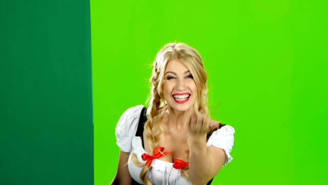 Girl in bavarian costume lures to their hand and showing the thumb. Green screen video