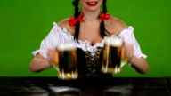 Girl in Bavarian costume pouring beer. Green screen. Slow motion video
