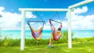 Girl in Bermuda Sitting on Colorful Hammock Overlooking Tropical Ocean video