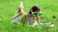Girl in big sunglasses in the shape of hearts with tablet pc lies on green grass video