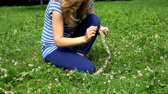 girl in blue weave head circlet from clover plant flowers video