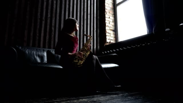 Girl in dress plays saxophone on black leather couch in retro room near window video