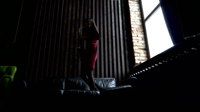 Girl in dress plays saxophone standing on black leather couch in retro room near window video