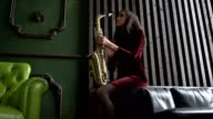Girl in dress with saxophone on black leather couch in retro room near window video