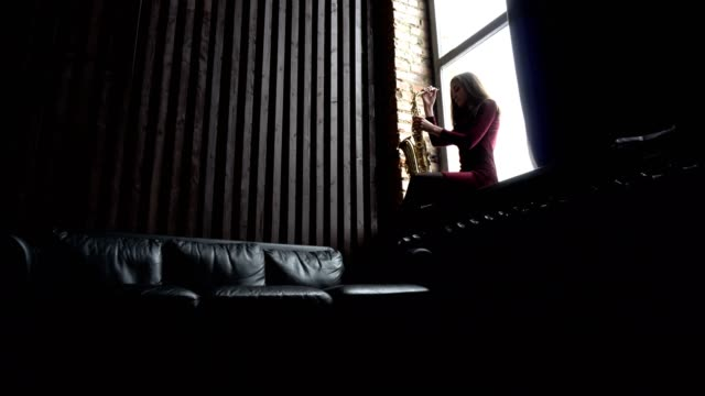 Girl in dress with saxophone on sitting on windowsill in retro room near window video