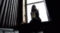Girl in dress with saxophone on sitting on windowsill in retro room near window video