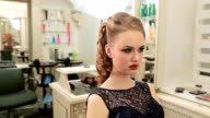 Girl in evening fashion dress during makeup and hairstyle looks in the mirror video