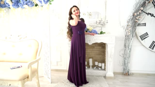 Girl in evening gown smiles on the background luxurious interior video