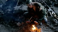 girl in military uniform, heated by the fire in the destroyed building video