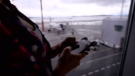 Girl in plaid shirt looks messages from friends, then checks email at the airport against the window in which the visible plane and a snowy field video