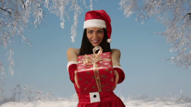 girl in red santa hat giving gift video