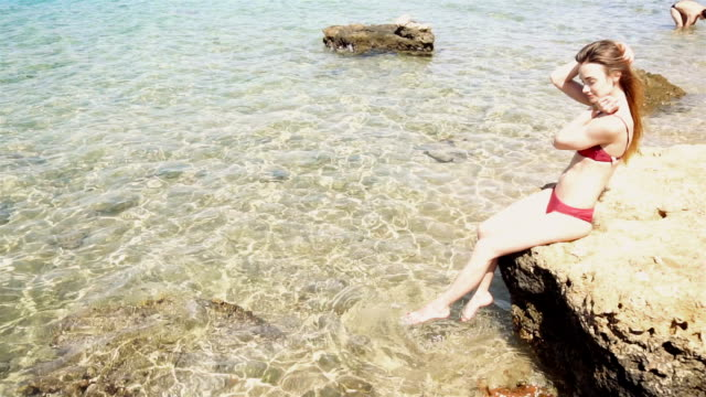 girl in red swimsuit sits on the rock and Flops feet in the water video