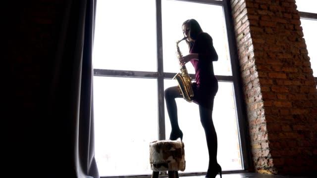 Girl in short dress plays saxophone in retro room near big window video