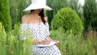 Girl in sun hat and dress among green trees and grass. video