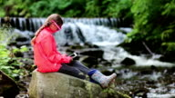 Girl in sunglasses in the shape of hearts with tablet pc sits near small river video