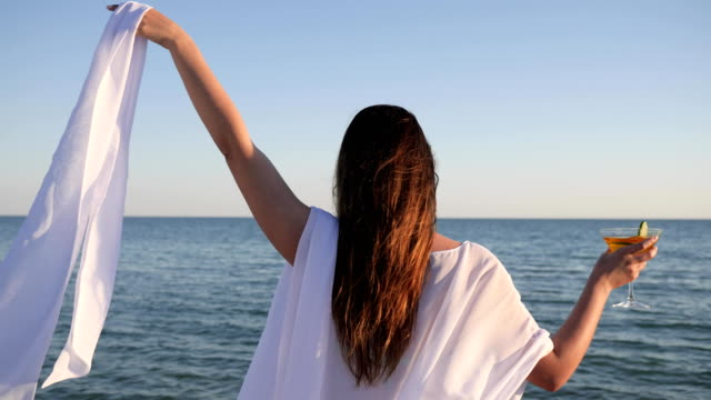 girl in Swimsuit on shore, women on background water Waving white cloth, holiday near ocean, female drinking Colored cocktail video