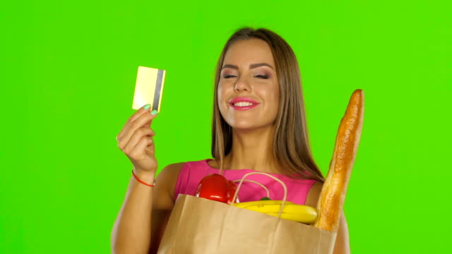 Girl in the calculation for the products used the gold card. Green screen. Close up video