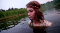 Girl in vintage white lace dress standing in a lake video