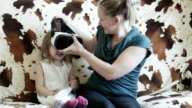 Girl in VR goggles on sofa with mother video