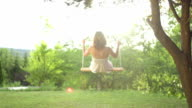 Girl in white dress swinging on a rope swing video