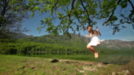 Girl in white dress swinging on rope swing by lake video