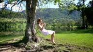 Girl in white dress swinging on rope swing by lake video